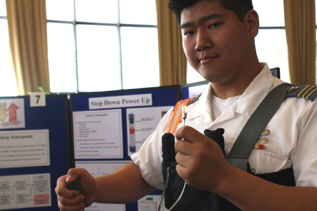 Firstie Daniel Lee demonstrates how simple movement, such as shaking a canister, can generate power to light a small lightbulb while presenting an invention designed to use Soldiers' motion to charge batteries during the Projects Day presentations April 30. Lee and Firsties Tossapol Sakawkanokrat, John Wagner and Jacob Weber designed the device, which is worn around the chest.