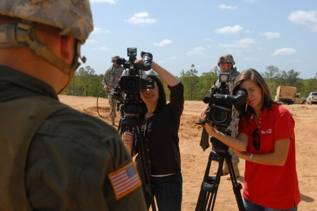 Reporters Stefaine Tiso (left) and Ashley Ball (right) interview Spc. Andrew Gould, an artilleryman assigned to Battery A, 1/10 FA, 3rd HBCT, during a break in training at a range on Fort Benning, April 28.