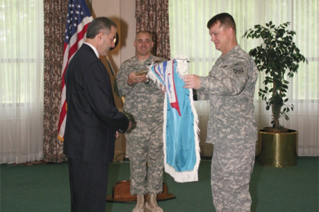Sgt. Maj. Billy Chaney, senior enlisted leader for Army Training Support Center, holds the guidon as Luciano Iorizzo, executive director for ATSC, watches Col. Paul Funk II, deputy commander Combined Arms Center-Training,  unfurl the new colors during the reflagging and patch changing ceremony April 30 at the Fort Eustis Club.