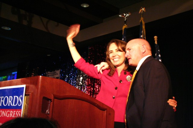 Rep. Gabrielle Giffords, congresswoman from Arizona's 8th district, and husband Navy Capt. Mark E. Kelly, an astronaut, wave to supporters together on the campaign trail. Giffords says being married to a Navy officer means the two see much less of each other.