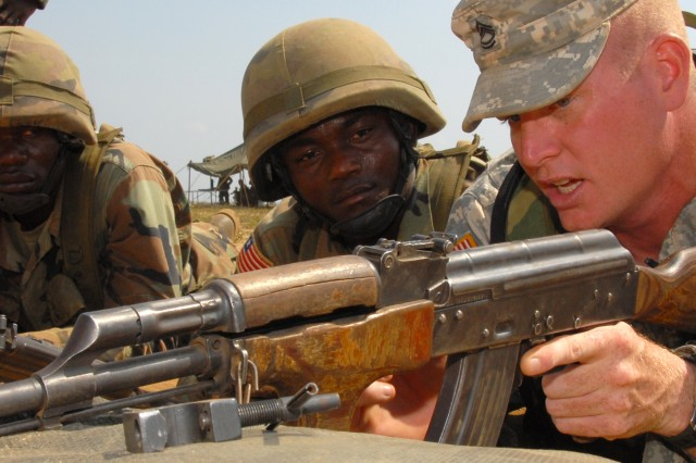 Under a scorching midday sun at Edward Binyah Kesselly barracks' AK-47 rifle range,  Sgt. 1st Class Eddie King, a U.S. Army Africa, mentor discusses the fundamentals of marksmanship with privates from the Armed Forces of Liberia.