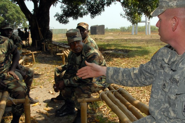 Under the shade of a mango tree, Sgt. 1st Class Eddie King, a U.S. Army Africa NCO, discusses the leadership development school that U.S. Army NCOs attend with privates from the Armed Forces of Liberia.