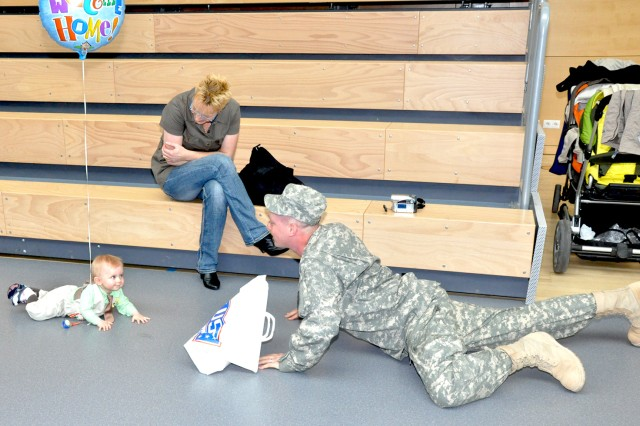 Capt. Ben Samuel plays with his 9-month-old son Jeremy during the welcome home event for the 209th Army Liaison Team at the Wiesbaden Fitness Center May 5. The 7th Civil Support Command unit served for more than a year, in and around Baghdad, Iraq, in support of Multi National Force-Iraq.