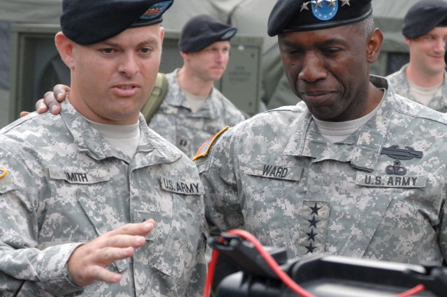 """Sgt. Jonathan Smith, a 509th Signal Battalion noncommissioned officer tasked to support U.S. Army Africa, briefs Gen. William """"Kip"""" Ward, commander of U.S. Africa Command on the advanced communication gear he uses in U.S. Army Africa's deployable command center."""