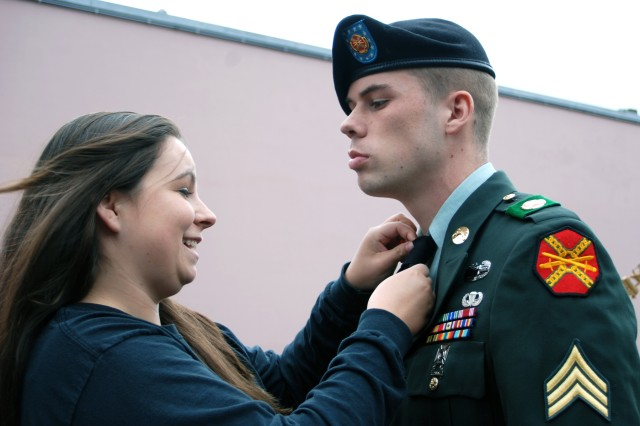 Robyn Strick straightens her husband Timothy's tie, after a Victory in Europe ceremony in Mons, Belgium, on Military Spouse Appreciation Day. She likes to support her husband at events when he is a member of the color guard. (May 8, 2009)