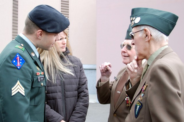 Sgt. Michael Lynch, and his wife Jillian, talk to two members of the 5th Fusiliers Battalion who fought with the First U.S. Army in the Battle of the Bulge 65 years ago. Lynch held the U.S. flag during the Victory in Europe Day ceremony in Mons, Belgium, on May 8, 2009.