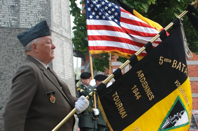 Frans Marique holds the 5th Fusiliers Battalion's colors at the base of the 1st Infantry Division monument in Mons, Belgium, alongside members of the USAG Benelux color guard. The monument honors the officers and men of the Big Red One who were killed from July 25, 1944, to Sept. 6, 1944, while fighting for the liberty of the world. WWII Veterans of the Belgian 5th Fusiliers Battalion attended the Victory in Europe Day ceremony on May 8, with the USAG Benelux to pay honor to those who helped liberate Belgium 65 years ago.