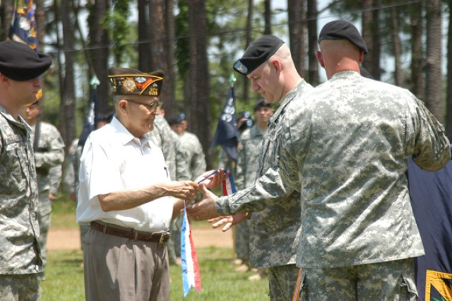 Retired Sgt. Maj. Steve Serna (left) presents a World War II campaign streamer to Col. Richard Bloss during the unit's activation ceremony.