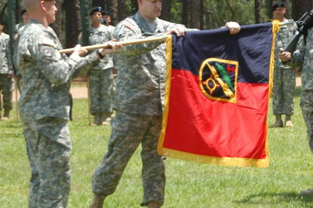 Col. Richard Bloss (right), outgoing commander of the 162nd Infantry Brigade, unfurls the unit colors, held by Brig. Gen. James Yarbrough, commanding general, Joint Readiness Training Center and Fort Polk, during a reactivation and change of command ceremony May 1 at Warrior Field. It is the first time the unit's colors have flown in 44 years.
