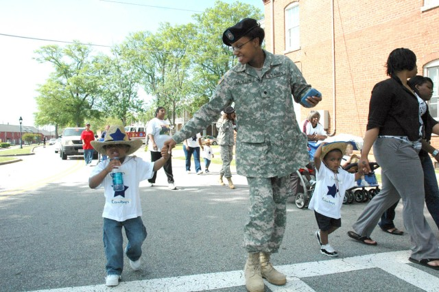 Isaiah Jackson, 3, takes a sip of water coming into the final stretch of the parade down Troop Row. Isaiah was accompanied by his mother, Spc. Taysia Jackson, a paralegal with the U.S. Army Central Staff Judge Advocate Group.