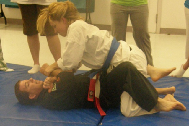 Camille Ronesi, a student at West Louisiana Jujutsu Training Academy in Leesville, grappels with Joe Harvey, owner and sensei of the dojo, at the Army Community Service Center April 28. Spouses observing the self-defense demonstration learned several helpful ways to get away from an attacker.