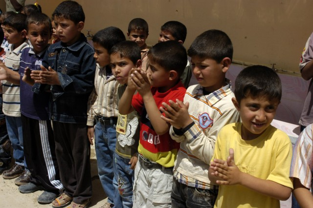 Iraqi children applaud after headmaster Yihya Mohammad Sultan's speech at a ceremony Monday April 27 thanking coalition forces for renovating their school.