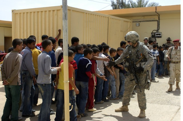 Iraqi children high five a U.S. Soldier, after a ceremony held Monday April 27 at their school. The ceremony's purpose was to thank coalition forces for renovating their school