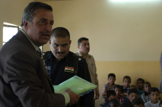 Headmaster Yihya Mohammad Sultan hands out Coalition educational care packages to his students after a ceremony Monday April 27 at their school. The ceremony's purpose was to thank Coalition Forces for renovating their school.