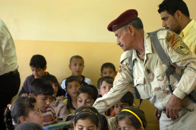 An Iraqi Sgt. Maj. hands out Coalition educational care packages to school students after a ceremony Monday April 27 at their school. The ceremony's purpose was to thank Coalition Forces for renovating their school.