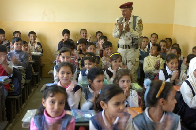 An Iraqi Sgt. Maj. and children applaud Coalition Forces for their assistance in renovating their school after a ceremony Monday April 27. The ceremony's purpose was to thank Coalition Forces for renovating their school.