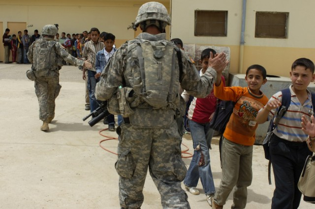 Iraqi children high five a U.S. Soldier after a ceremony held Monday April 27 at their school. The ceremony's purpose was to thank Coalition Forces for renovating their school.