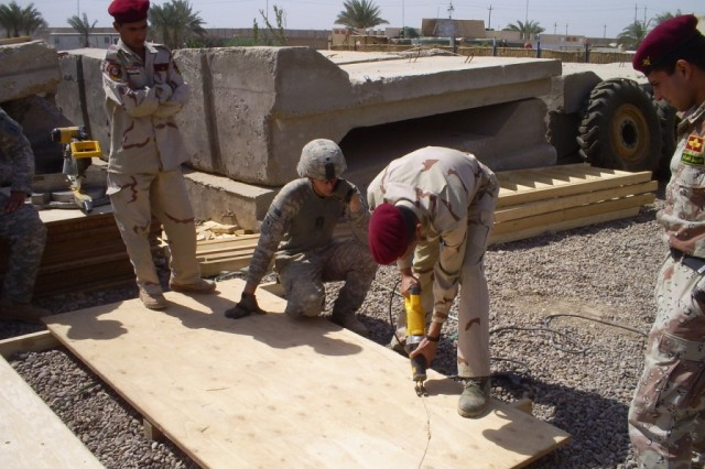 BAGHDAD - San Antonio native, Sgt. Mark Jordan, 46th Engineer Combat Battalion (Heavy), 225th Eng. Brigade, team leader, instructs a team of 23rd Iraqi Army Engineer Regiment Soldiers on how to outfit their concrete guard towers with wooden safety platforms. Prior to starting the project, the four guard towers had rickety ladders going to the main guard platform at the top of the tower.  At 15 feet above the ground, a fall could seriously injure a Soldier.