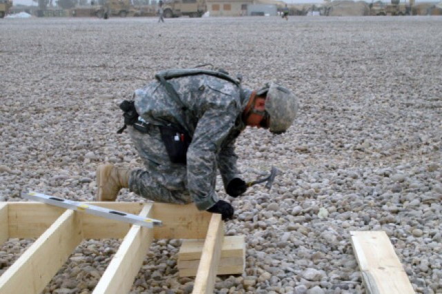 BAGHDAD - Spc. Chance Bailey from Russellville, Ark., a member of the 46th Engineer Battalion, 225th Eng. Brigade, nails together a floor system frame to prepare it for sheathing. The 46th Eng. Bn. is building 30 B-Huts, a dining facility extension and a food preparation area at Combat Outpost Carver, located in the southeastern outskirts of Baghdad, May 4. The project is being completed with future noncommissioned officers like Bailey in the lead to develop both their leadership and construction skills.