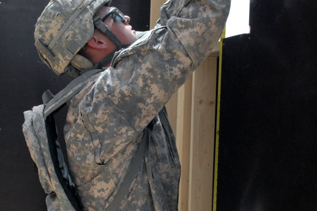 BAGHDAD - Spc. Miles McFarland from Portland, Ore., a member of the 46th Engineer Battalion, 225th Eng. Brigade, 1st Cavalry Division, measures the opening for an environmental control unit before he cuts plywood sheathing for the wall section. The 46th Eng. Bn. is building 30 B-Huts, a dining facility extension and a food preparation area at Combat Outpost Carver, located in the southeastern outskirts of Baghdad, May 4. This project is being led by future Army leaders like McFarland to test their knowledge and give them experience leading troops in combat operations.