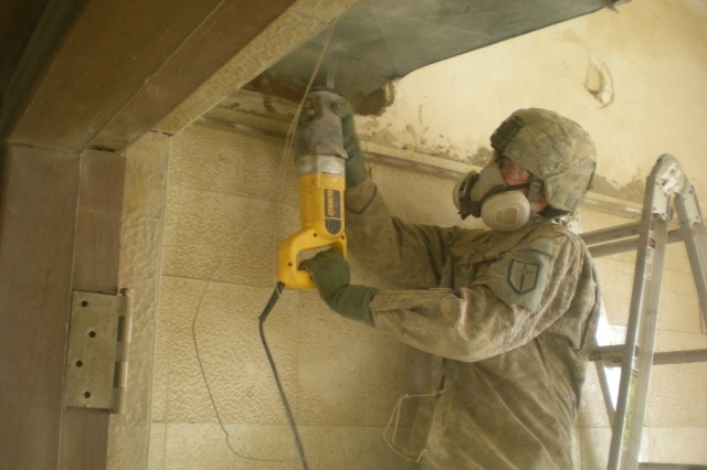BAGHDAD - Spc. James Ridgley from Gibsonburg, Ohio, carpenter, 46th Engineer Combat Battalion (Heavy), removes an existing duct system from the fifth floor of the high-rise building being renovated, April 30 at Joint Security Station Loyalty.