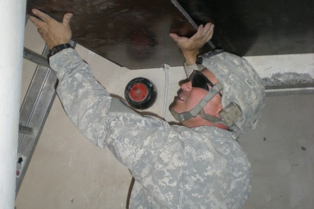 BAGHDAD - Sgt. Heith Kafer of Medford, Ore., carpenter, 46th Engineer Combat Battalion (Heavy), 225th Engineer Brigade, places plywood on the ceiling of the seventh floor stairwell landing April 22 at Joint Security Station Loyalty. The project provided 72 rooms outfitted with ballistic protection and improved exits to meet modern building requirements and now offers 24,000 square feet of finished living space for the paratroopers of the 82nd Airborne Division.