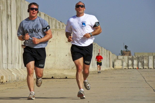"Capt. Kenneth Evans and 1st Lt. Andrey Postrigan, 5th Battalion, 82nd Field Artillery Regiment, 4th Brigade Combat Team, 1st Cavalry Division, run the ""Mighty Maysan Marathon"" on Forward Operating Base Hunter recently."