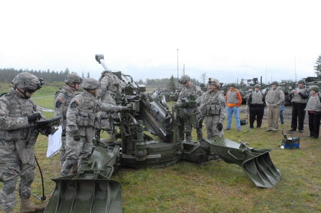 Soldiers from 4th, Brigade, 2nd Infantry Division demonstrate the procedures for firing an M-777 howitzer when a groupd from Lakewood, Wash. visited the unit.