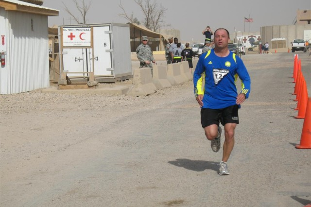 "Sgt. 1st Class Chris Baker, 287th Sustainment Brigade postal noncommissioned officer in charge, native of Quincy, Mass. crosses the finish line at the Boston Athletic Association-sanctioned ""Boston Marathon in Iraq"" at Contingency Operating Base Adder, Iraq, April 18.  Baker placed fourth overall with a time of 3 hours, 24 minutes and 40 seconds"