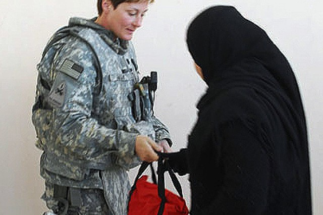 BAGHDAD - Lt. Col. Anne Resty, of Clarinda, Iowa, brigade physical therapist, and Women's Initiative Coordinator, Company C, 47th Forward Support Battalion, 2nd Brigade Combat Team, 1st Armored Division, Multi-National Division-Baghdad, hands out a kit of hygiene and health products at the women's health conference coordinated by the 445 Civil Affairs Battalion of 1st Combined Arms Battalion, 63rd Armor Regiment, 2nd BCT, 1st Armd. Div,, MND-B, at Omar Almukhtar High school in Mahmudiyah, Feb 18.