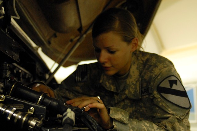 Spc. Marie MacDonald, from Chattanooga, Tenn., UH-60 Black Hawk helicopter mechanic, 615th Aviation Support Battalion, 1st Air Cavalry Brigade, 1st Cavalry Division, carefully performs a maintenance check on the avionics system of a Black Hawk at Camp Buehring, Kuwait, May 7, as the battalion readies its aircraft for their upcoming deployment to Iraq