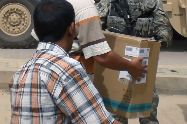 BAGHDAD -Staff Sgt. Dane Halligan, a native of Sauquoit, N.Y., 403rd Civil Affairs Battalion, hands a box of baseball equipment to a local Iraqi at the Karkh Ministry of Youth and Sports May 7. The battalion, along with elements of the 2nd Heavy Brigade Combat Team, 1st Infantry Division, Multi-National Division - Baghdad, gave enough donated baseball equipment to be use on three playing fields in the Karkh district of northwest Baghdad.