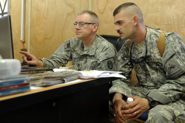 BAGHDAD - Sgt. 1st Class Cameron Mills (left), from Raleigh N.C., information operations non-commissioned officer in charge, Headquarters and Headquarters Company 30th Heavy Brigade Combat Team, asks questions of his counterpart Sgt. 1st Class David McGuire, of Crofton, Ky. information operations NCOIC, HHC, 2nd Brigade Combat Team, 1st Armored Division, Multi-National Division-Baghdad, shortly after he and other 30th HBCT Soldiers began to arrive at Forward Operating Base Falcon, May 6.