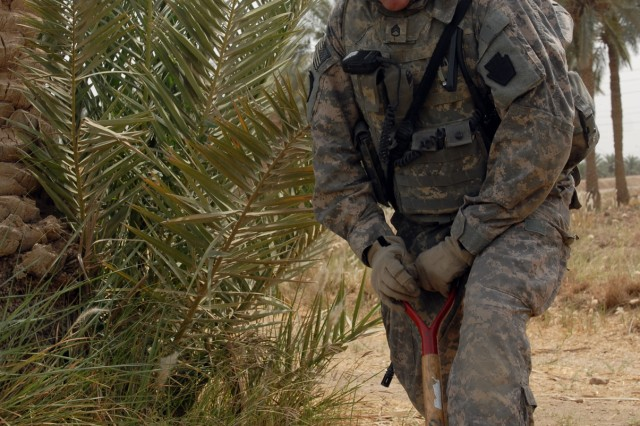 BAGHDAD - Staff Sgt. Paul Jones, a Waynesboro, Pa., native and cavalry scout squad leader assigned to C Troop, 2nd Squadron, 104th Cavalry Regiment, 56th Stryker Brigade Combat Team, digs up a possible weapons caches in Hay al-Skri here, May 8.