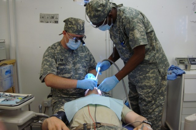 Capt. Daniel Roberts, an Army dentist, and Spc. Dan Curry, a dental hygienist, both from the 27th Brigade Support Battalion, 4th Brigade Combat Team, 1st Cavalry Division, remove four impacted wisdom teeth from a Long Knife Brigade Soldier. The dental practitioners work hand in hand with the 464th Dental Company and the 10th Combat Support Hospital.