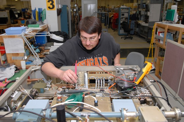 Tony Taylor, electronics mechanic, performs electrical testing and alignment on AN/MST-T1(A)  transmitter.