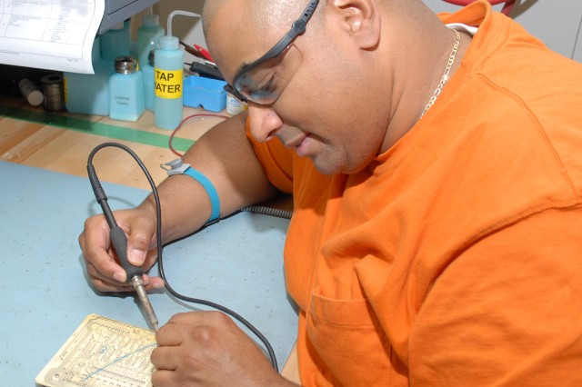 Julio Asencio, electronics mechanic troubleshoots and repairs a circuit card for the AN/MST-T1(A) MUTES.