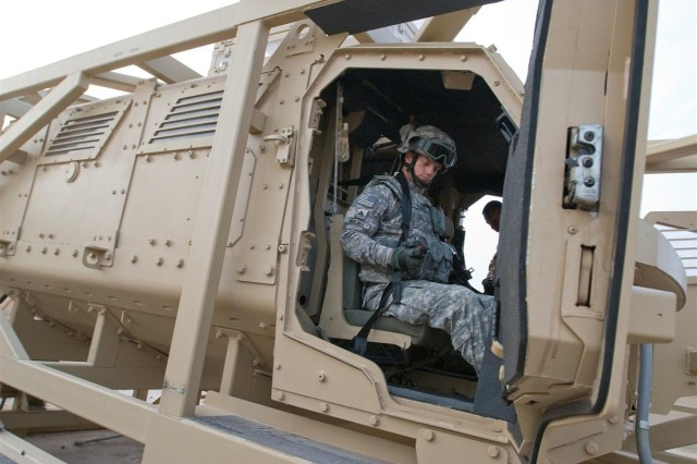 Sgt. David A. Boling, the S-2 noncommissioned officer in charge for the 49th Movement Control Battalion, fastens his seatbelt in a Mine-Resistant Ambush-Protected Egress Trainer at Camp Buehring, Kuwait, May 1. Camp Buehring is among the first locations to receive the new egress trainers.