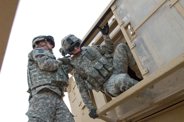 Sgt. Chris J. Kimble, an S-3 noncommissioned officer with the 49th Movement Control Battalion, helps Sgt. David A. Boling, the S-2 noncommissioned officer in charge with the 49th Movement Control Bn., out of the Mine-Resistant Ambush-Protected Egress Trainer at Camp Buehring, Kuwait, May 1.
