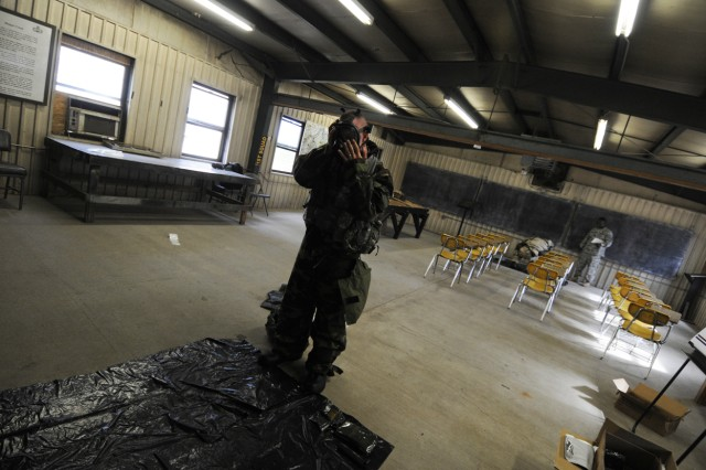 Spc. Sean Mills, of Co. D, 1st Battalion, 508th Parachute Infantry Regiment, 4th BCT, 82nd Airborne Division, prepares to decontaminate himself against a chemical attack while dressed in his Mission Oriented Protective Posture suit, during the warrior tasks and drills portion of the 2009 82nd Airborne Division NCO & Trooper of the year competition May 7.