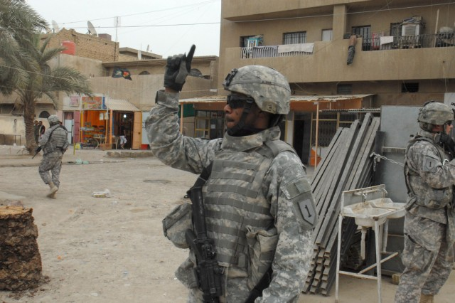 BAGHDAD - Staff Sgt. Trowny Alexis of Miami, signals for the Soldiers of Battery A, 1st Battalion, 7th Artillery Regiment, to mount up at the end of a patrol in a commercial district of the Mutanabi neighborhood of Baghdad May 8. The Soldiers arrived on a tip that a terrorist was in the area, but the suspect fled prior to the Soldiers' arrival.