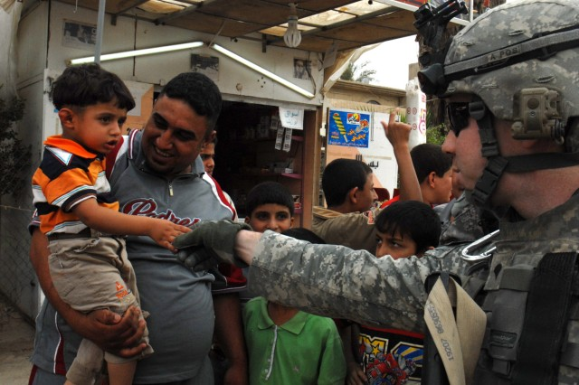 """BAGHDAD- Spc. Ryan Chapman, Battery A, 1st Battalion, 7th Field Artillery Regiment, shakes hands with an Iraqi boy in the Mutanabi neighborhood of Baghdad May 8. """"I have a soft spot for the kids, especially the little ones,"""" said the native of Olathe, Kan."""