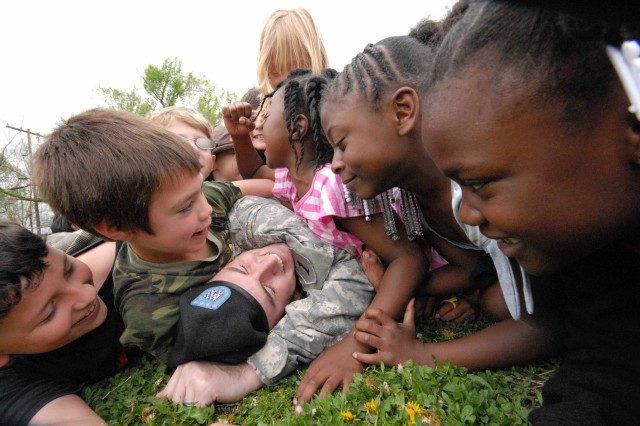"""Sgt. James Kinney; 1st Bn; 16th Infantry gets dog piled by students at Westwood Elementary Schoool as part of the school's """"Schools in Review"""" program there April 29, 2008"""