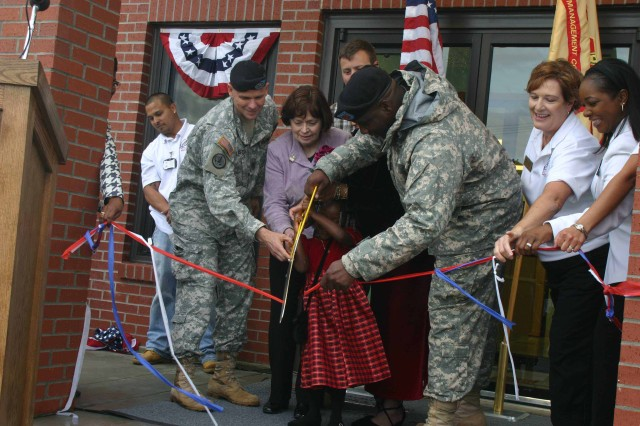 Col. Richard Piscal, Garrison Commander, M.A. Lucas, director of CYSS Headquarters, and Sgt. Timothy Holden, HHC, 1st Sust. Bde., and his daughter, Aliesia, 4, cut the ribbon during the opening of the Warren East child development center.  Warren East will offer hourly and part-day services for Famililes registered with CYSS.
