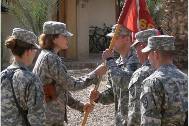 Capt. Robert Richard, a Laplata, Md. native, accepts the 68th Transportation Company's colors from 419th Combat Sustainment Support Battalion Commander Lt. Col. Kristan Hericks, a native of Irvine, Calif., during a change of command ceremony at Camp Taji, Iraq April 3. The transfer of colors symbolically represents entrusting the incoming commander from the outgoing commander to lead their unit. Maj. Donna Johnson, a native of Columbus, Ohio, has completed her command as commander of the 68th Trans. Co. and will continue on with her military training school required for her promotion.