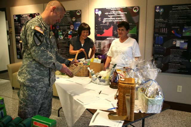 Lt. Col. Robert J. Phillips browses items before placing a bid on a gift certificate to a local restaurant as K.C Bertling (middle) and Sarah Trial, AER coordinators for USASMDC/ARSTRAT, assist.