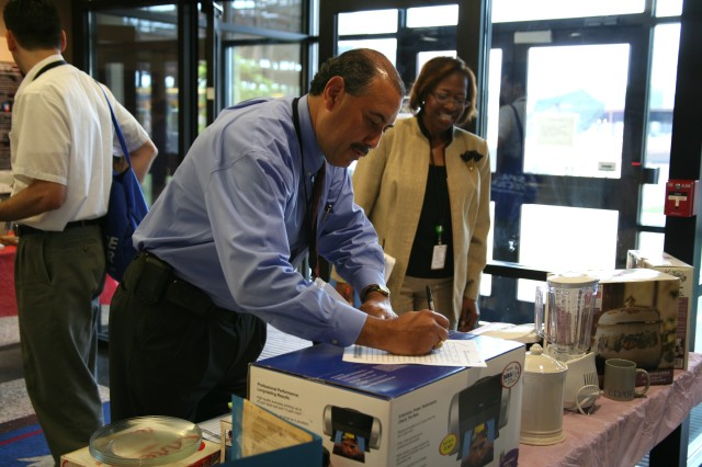 Mario Ares places a bid on a color ink jet printer during the White Elephant Sale May 7 at USASMDC/ARSTRAT.