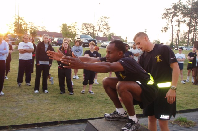 Sgt. 1st Class Kwame Pettus (squatting), and Cpt. Joe Luchetta, of Company A, 407th Brigade Support Battalion, 2nd Brigade Combat Team, 82nd Airborne Division, show unit spouses  the proper way to perform some exercise techniques during the physical training portion of the 407th's Spouses Day held May 5. (courtesy photo)
