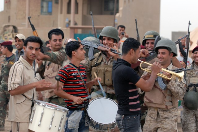 BAGHDAD - A small band, along with Soldiers of the 45th Iraqi Army Brigade, celebrate a goal by the home team during the Combined Forces Football Tournament, in the Salman Pak community, May 10. The game was met with enthusiasm and support from the local community, who showed up to watch the game.