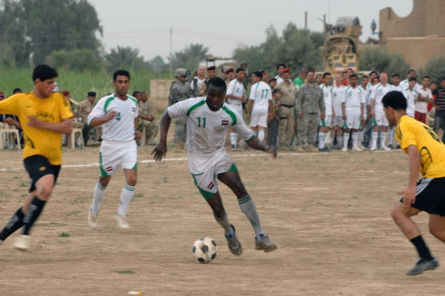 BAGHDAD - Jamaica native, Pfc. Mark Skeen, assigned to 1st Battalion, 505th Parachute Infantry Regiment, moves the ball toward the goal, flanked by defenders. Skeen's team, made up of 505th Soldiers and the 45th Iraqi Army Brigade, lost 3-2.